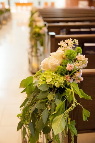 roses-and-green-leaves-on-church-pews-for-wedding-ceremony
