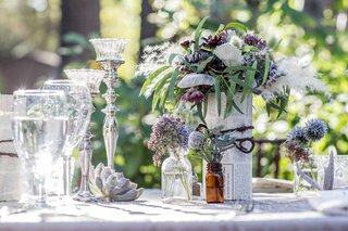 wildflower-centerpieces-wildflowers-in-bookpages-and-small-bottles-silver-candlesticks