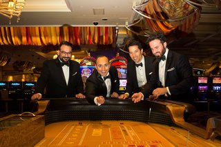 groom-and-groomsmen-in-classic-tuxedos-at-gambling-table-in-casino