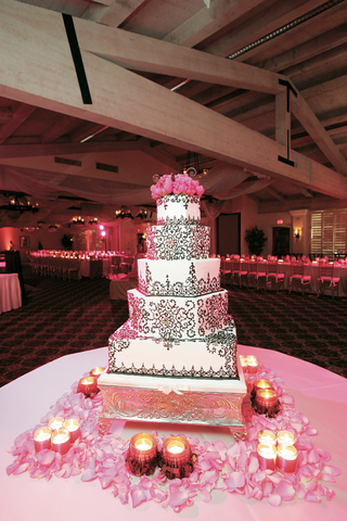 white-cake-with-chocolate-scroll-work-and-pink-flower-topper