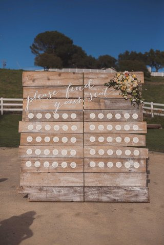 circle-escort-cards-on-rustic-wood-board-with-calligraphy-please-find-your-seat-and-flowers