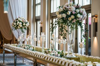 wedding-reception-mirror-gold-table-candles-tall-flower-arrangements-escort-cards-gold-boxes-favors