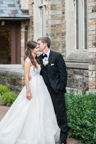 a-groom-kissing-his-beautiful-bride-on-the-cheek-during-their-first-look-before-the-church-ceremony