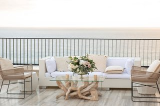 wedding-reception-lounge-area-driftwood-coffee-table-vase-with-eucalyptus-leaves-flowers-white-pink
