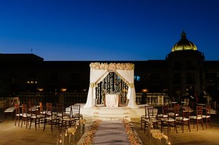chuppah-with-white-drapery-blush-and-ivory-roses-and-hanging-orchids-lighting-night-ceremony