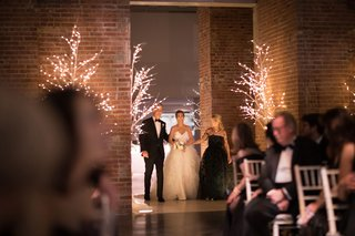 brick-wall-led-trees-winter-wedding-bride-entering-ceremony-space-with-father-and-mother-black-dress