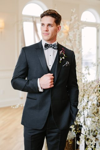 groom-in-black-suit-with-black-grey-and-white-floral-bow-tie-and-matching-pocket-square