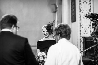 black-white-photo-of-bride-in-an-off-the-shoulder-black-dress-feather-headpiece-at-altar-groom