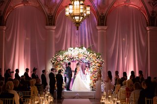 bride-and-groom-at-the-breakers-wedding-ceremony-flower-arch-chuppah-jewish-wedding-pink-lighting