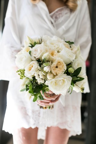 bride-in-white-robe-holding-ivory-bridal-bouquet-garden-rose-rose-berries-greenery-elegant-classic
