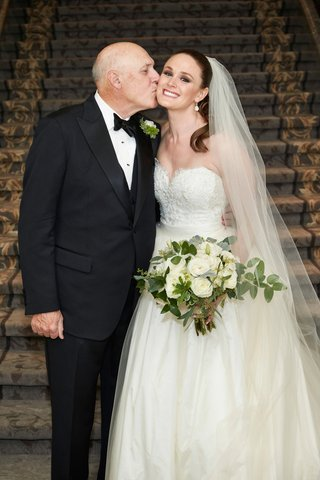 father-of-bride-in-tuxedo-bow-tie-kissing-daughter-bride-on-cheek-strapless-bridal-gown