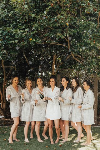 bridesmaids-in-greey-robes-bride-in-lace-sleeeve-robe-popping-champagne-seattle-wedding