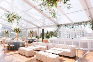 clear-tent-wedding-reception-flower-chandelier-tufted-lounge-furniture-white-gold-tables-bar-shelves