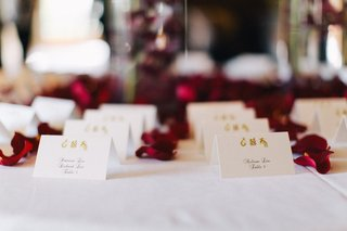 wedding-reception-place-card-table-with-white-cards-with-chinese-characters-red-flower-petals