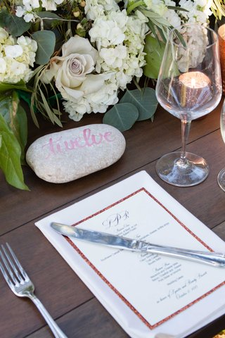 wood-reception-table-with-rose-gold-menu-green-and-white-flower-arrangement-and-grey-stone-with-pink
