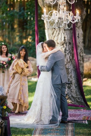 bride-in-a-claire-pettibone-dress-with-gold-and-silver-embroidery-veil-kisses-groom-in-grey-suit