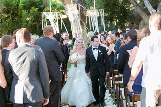 bride-in-a-strapless-hayley-paige-dress-beaded-belt-tiered-skirt-walks-up-aisle-with-groom