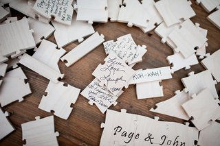 guests-signing-puzzle-pieces-to-fit-with-bride-and-grooms-proposal-and-puzzle