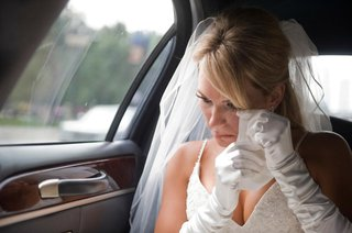 a-bride-in-a-veil-gloves-and-spaghetti-strap-dress-dabs-at-her-eyes-with-a-handkerchief