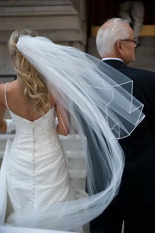 bride-in-veil-and-spaghetti-strap-dress-with-embroidered-bodice-with-father-outside-the-church