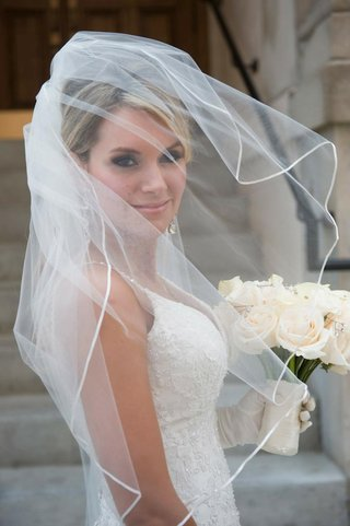 bride-in-a-veil-and-spaghetti-strap-dress-with-embroidered-bodice-holds-bouquet-of-white-flowers