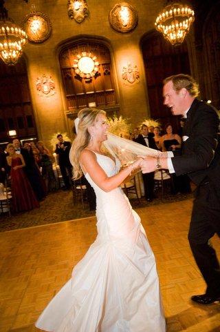 bride-in-a-spaghetti-strap-gown-dances-with-groom-in-black-tuxedo