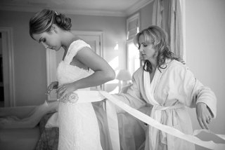 black-and-white-photo-of-bridesmaid-tying-wedding-belt