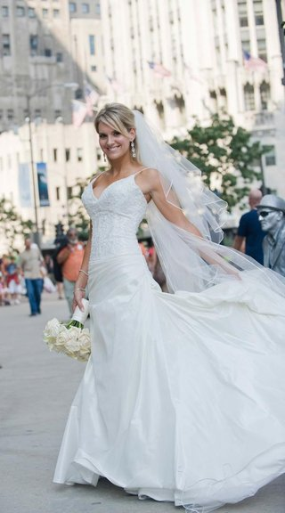 bride-in-a-veil-and-gown-with-a-thin-strapped-beaded-bodice-and-full-skirt