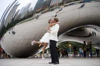 bride-in-short-dress-kisses-groom-in-tuxedo-of-white-coat-and-black-pants-in-millennium-park