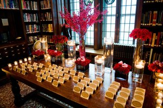 wedding-reception-place-card-table-decorated-with-red-roses-fuchsia-flowers-and-floating-candles