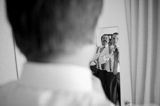 black-and-white-photo-of-groom-looking-in-mirror