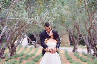 bride-in-monique-lhuillier-crop-top-wedding-dress-held-by-groom-in-armani-standing-under-trees