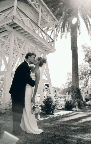 black-and-white-photo-of-couple-kissing-under-palm-tree
