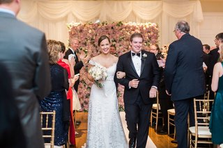 bride-in-legends-romona-keveza-off-shoulder-wedding-dress-with-groom-arm-in-arm-flower-wall