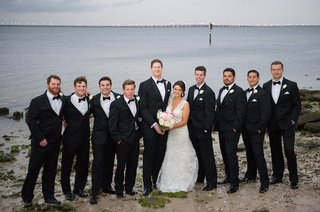 bride-and-groom-with-men-on-beach-bay-in-florida