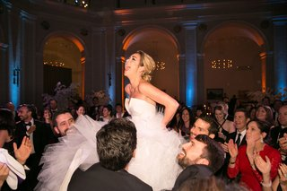 bride-on-chair-during-hora-at-jewish-wedding-in-brooklyn-at-museum-venue