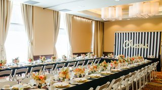 wedding-shower-with-black-tablecloths-white-chairs-and-white-pink-and-orange-flowers