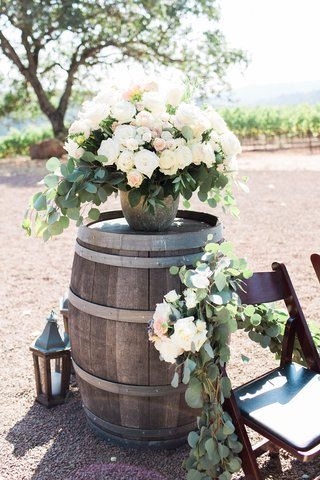 ceremony-seating-with-fresh-greenery-and-white-flowers-wine-barrel-lantern-bouquet-of-flowers-blush