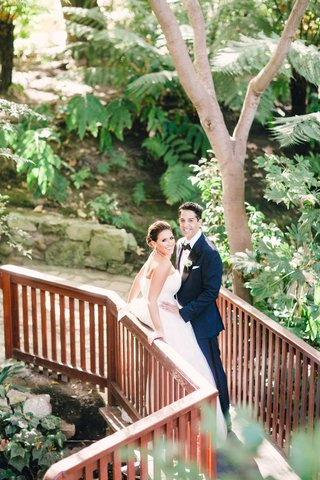 bride-in-vera-wang-wedding-dress-and-groom-in-blue-tuxedo-at-hotel-bel-air-bridge