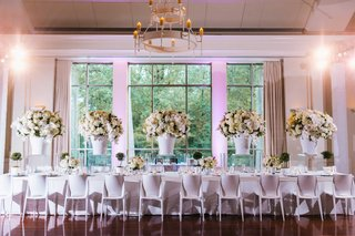 head-table-with-white-chairs-white-linen-lucite-risers-white-ginger-jar-centerpieces-flowers