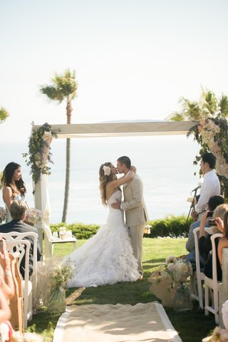 katrina-hodgson-and-brian-scott-kiss-under-wedding-arch