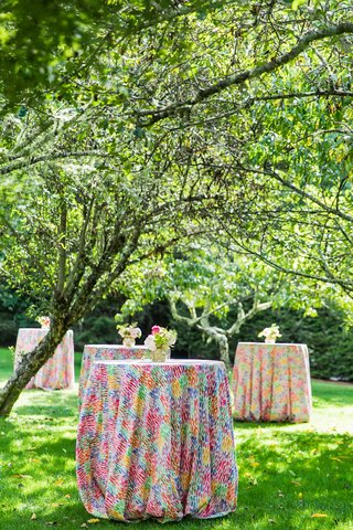 wedding-reception-outdoor-cocktail-hour-bright-multi-colored-linens-on-cocktail-tables-trees