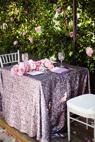 wedding-reception-sweetheart-table-with-purple-sequined-tablecloth-and-roses-by-leafy-hedge