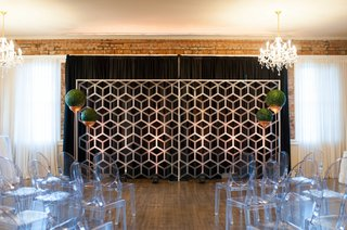 a-contemporary-style-ceremony-space-including-geometric-backdrop-spherical-arrangements-ghost-chairs