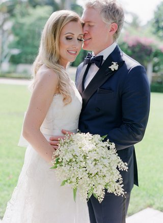 wedding-portrait-bride-with-long-blonde-hair-curled-white-wedding-dress-lily-of-the-valley-bouquet