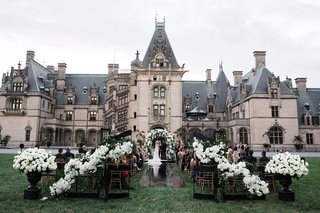 wedding-ceremony-with-black-wrought-iron-gates-white-flowers-black-aisle-runner-outdoors-castle