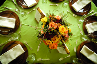 wedding-reception-centerpiece-of-orange-and-yellow-roses-and-greenery