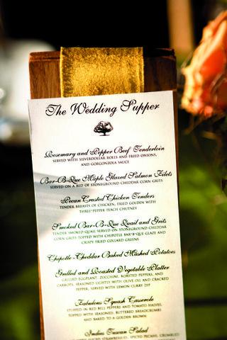 wedding-reception-menu-displayed-on-wood-board-with-golden-ribbon