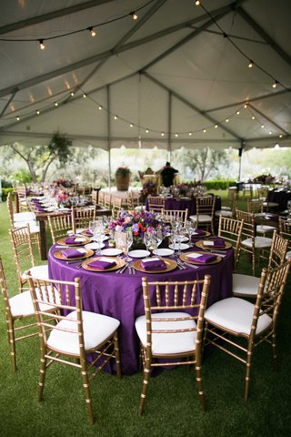 purple-table-linens-gold-charger-plates-colorful-floral-centerpieces-gold-chairs-tented-reception