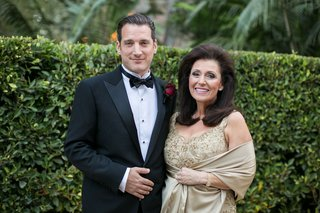 mother-of-the-groom-wearing-sleeveless-champagne-beaded-evening-gown-with-tan-wrap-with-groom-in-tux